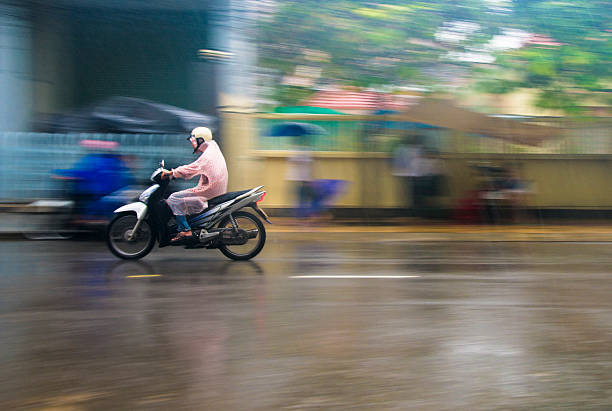 riding a motorcycle through a storm in nha trang, vietnam - motorbike, umbrella stock pictures, royalty-free photos & images