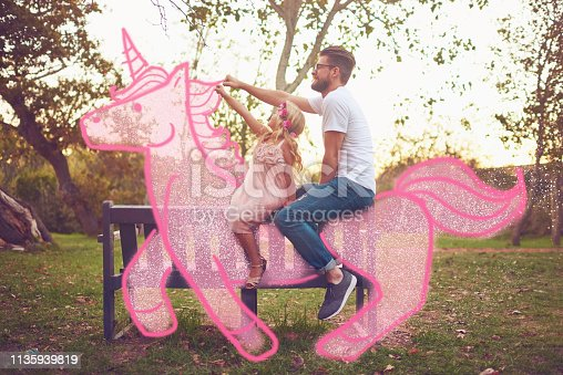 Shot of a happy father and daughter riding a pink toy unicorn together in a park outdoors