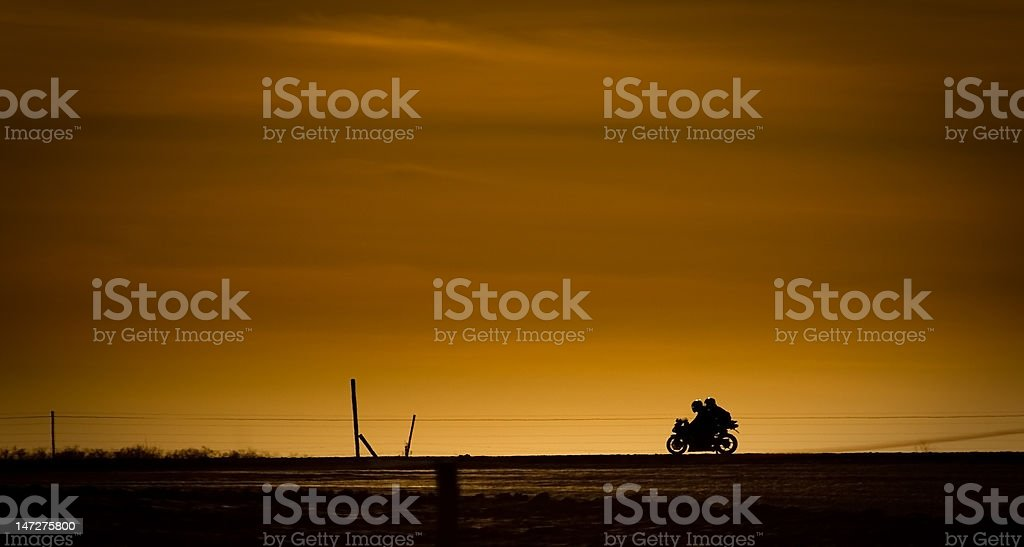 Motor bike in on a road in the sunset