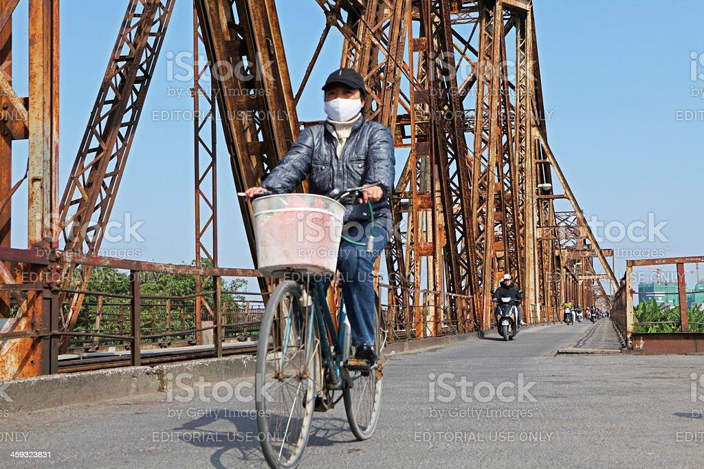Riding bicycle on Long Bien bridge stock photo