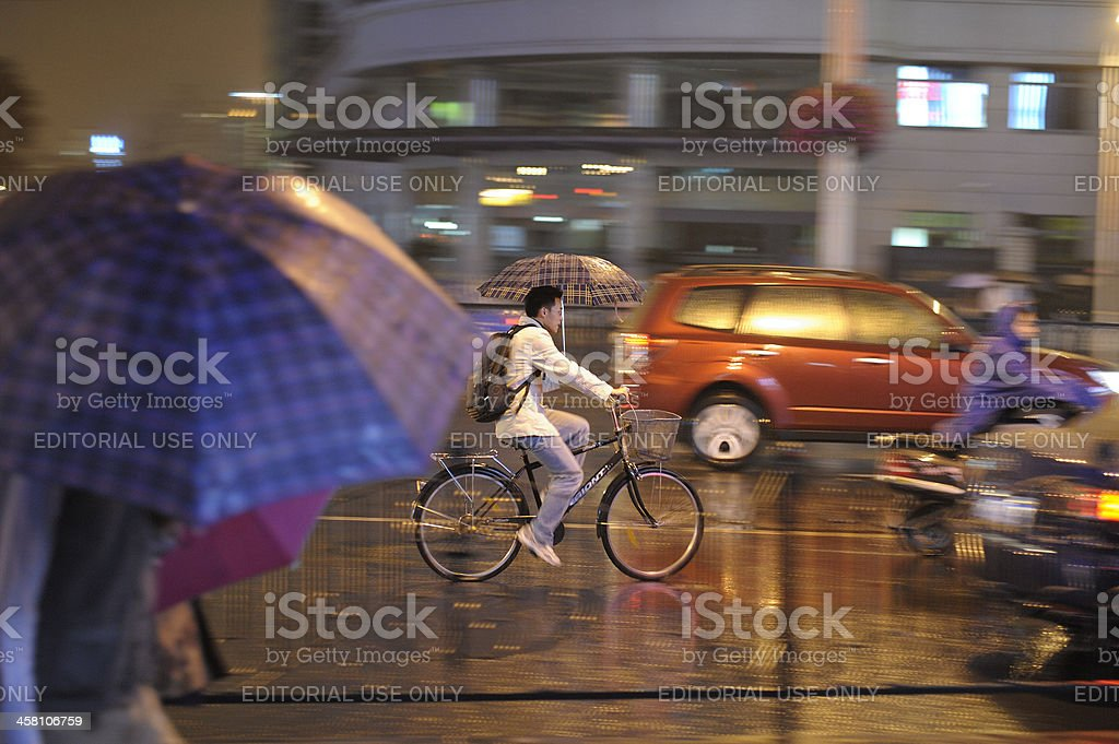 Riding bicycle with umbrella stock photo