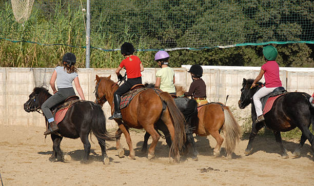 riding children group of children horseback riding on their shetland ponies pony stock pictures, royalty-free photos & images