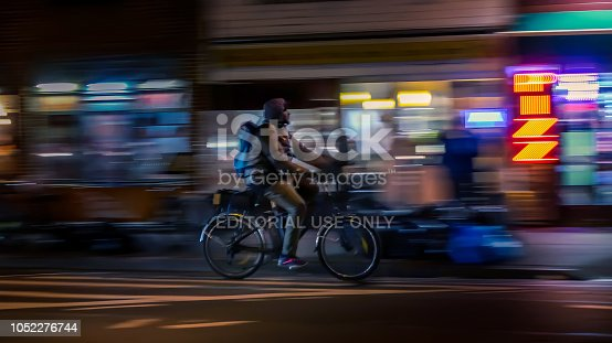 929609038istockphoto Riding cyclists. Bicyclistsin in city, night, abstract. Modern active lifestyle, healthy lifestyle concept. Motion blurred 1052276744