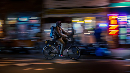 929609038 istock photo Riding cyclists. Bicyclistsin in city, night, abstract. Modern active lifestyle, healthy lifestyle concept. Motion blurred 1052276744