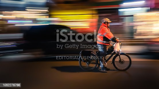 929609038istockphoto Riding cyclists. Bicyclistsin in city, night, abstract. 1052276766