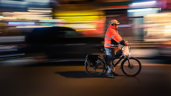 929609038 istock photo Riding cyclists. Bicyclistsin in city, night, abstract. 1052276766