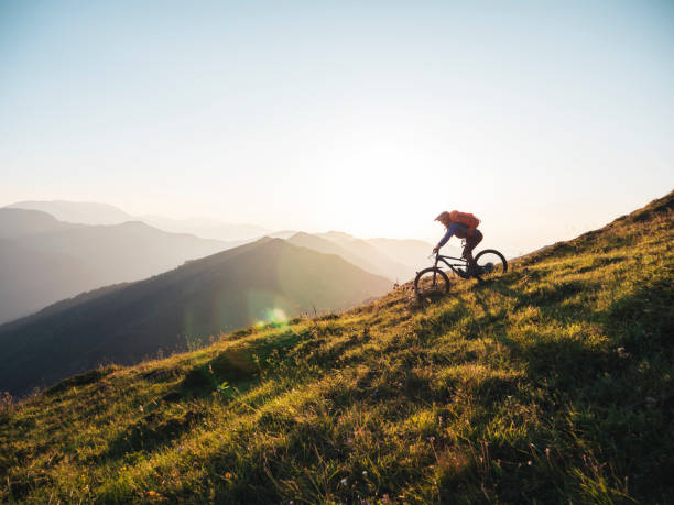 Riding Downhill In The Mountains At Sunset. Mountain biker riding downhill in the mountains. mountain biking stock pictures, royalty-free photos & images