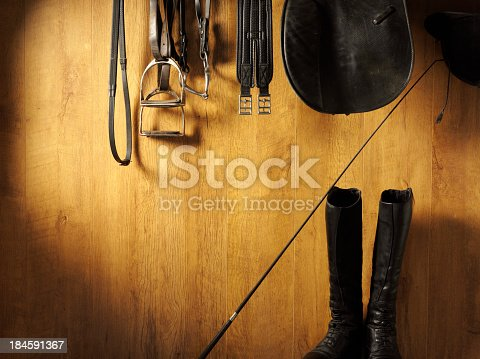 Equestrian riding boots and equipment hanging on a wooden background with copy space.Click on the link below to see more of my sport images