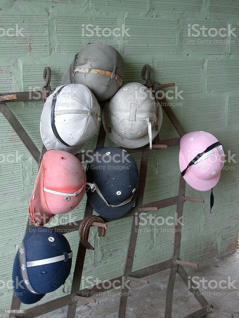 Riding hats and polo helmets in a stable stock photo