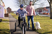 A boy with down syndrome rides his bike through a residential district whilst his father walks beside him with the dog.