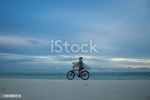 istock Riding Home with Surfboard 1284685318