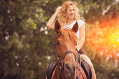 Blond hair woman riding horse on sunny day