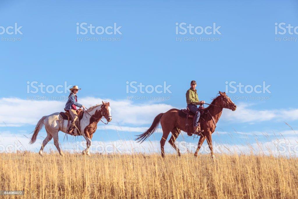 Riding Horseback Across Grassy Prairie stock photo