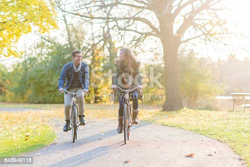 A Caucasian couple are outdoors on a sunny autumn day. They are wearing warm clothes. They are riding bikes on a trail together.