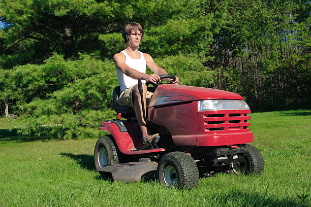 riding lawnmower cutting summer grass - riding lawn mower stock photos and pictures