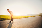 Young man riding longboard on the sreet, on a sunny day.