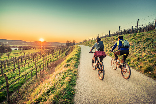 Biker couple riding moutain bike in the countryside at sunset