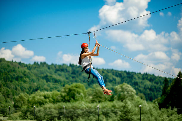 Riding on a zip line Young woman in casual wearing with red helmet riding on a zip line in the mountains. Active kind of recreation zip line stock pictures, royalty-free photos & images