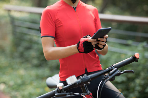 Riding on bike path,using smartphone while riding bike on sunny day stock photo