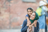 A mother wearing a hijab is holding her daughter up on her shoulders.
