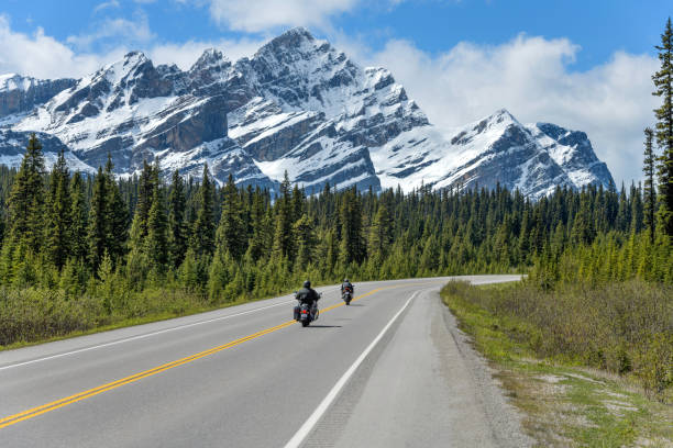 Riding On The Icefields Parkway - Two motorcyclists are enjoying the scenic ride on Icefields Parkway, with massive snow-covered Mount Patterson rising high in front of the road, on a sunny Spring day, Banff National Park, AB, Canada. stock photo