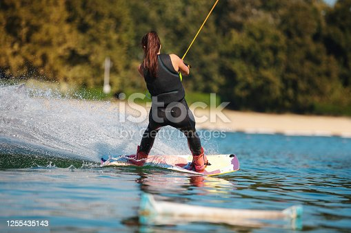 Rear view of a young woman holding towing rope for wakeboard ride and reclining backwards to make a splash on the lake