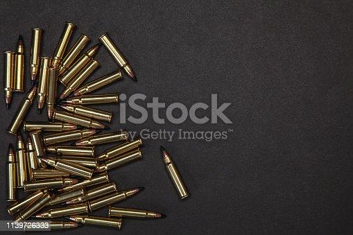 1043434568 istock photo Rifle cartridges on a black background 1139726333