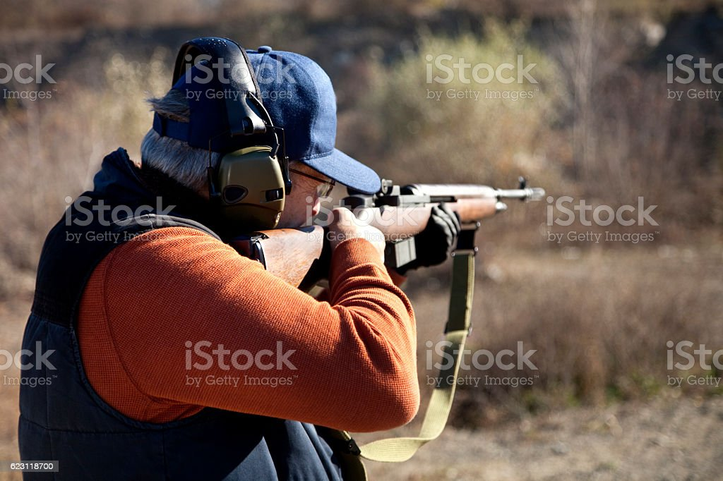 Rifle shooter aiming high powered rifle outdoors stock photo