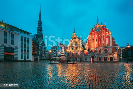 istock Riga, Latvia. Scenic Town Hall Square With St. Peter's Church, Schwabe House, House Of Blackheads During Night Rain. Popular Showplace With Famous Landmarks On It In Bright Evening Illumination In Summer Twilight Under Blue Sky. Riga, Latvia. Scenic Town 1321982874