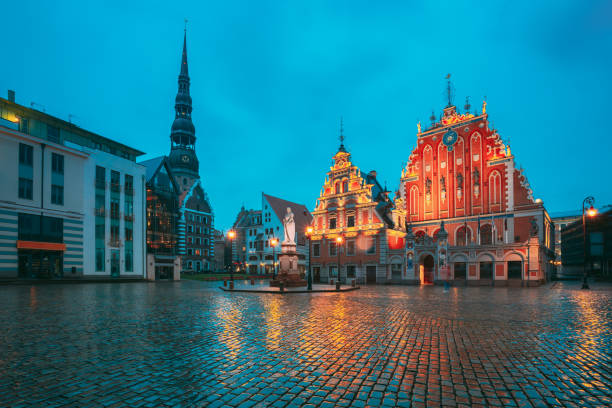 Riga, Latvia. Scenic Town Hall Square With St. Peter's Church, Schwabe House, House Of Blackheads During Night Rain. Popular Showplace With Famous Landmarks On It In Bright Evening Illumination In Summer Twilight Under Blue Sky. Riga, Latvia. Scenic Town stock photo