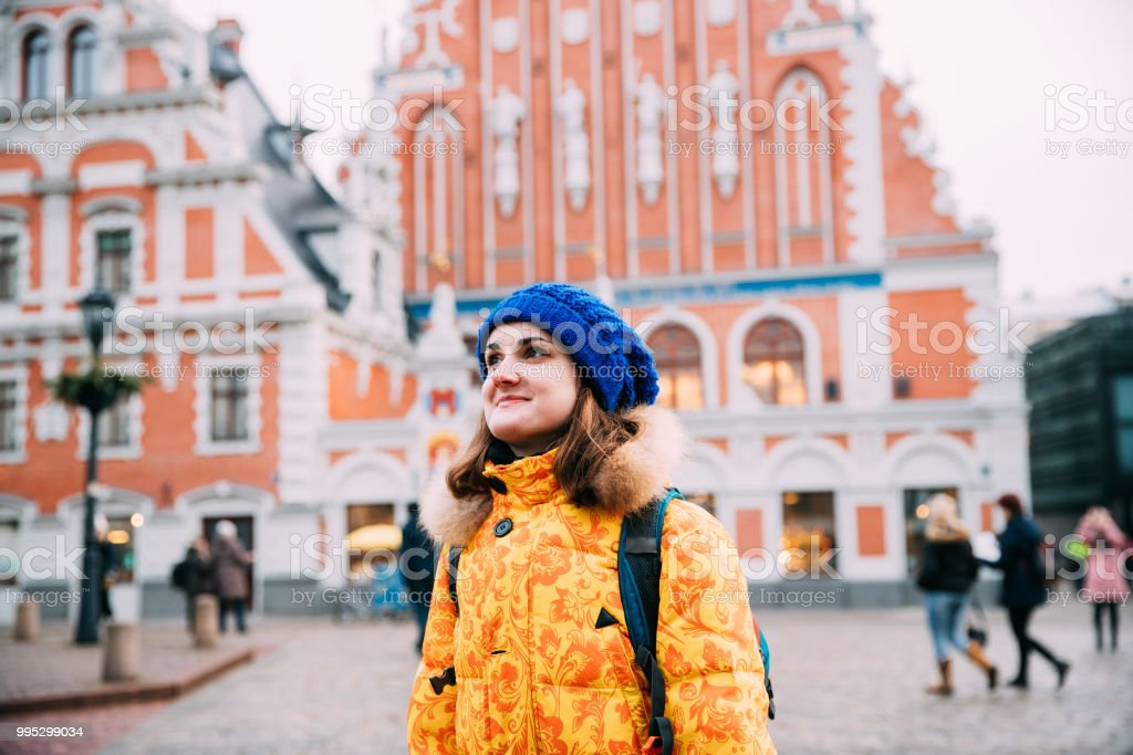 Riga, Latvia. Young Beautiful Pretty Caucasian Girl Woman Dressed In Yellow Jacket And Blue Hat Enjoying Life And Smiling On Background Blackheads House stock photo