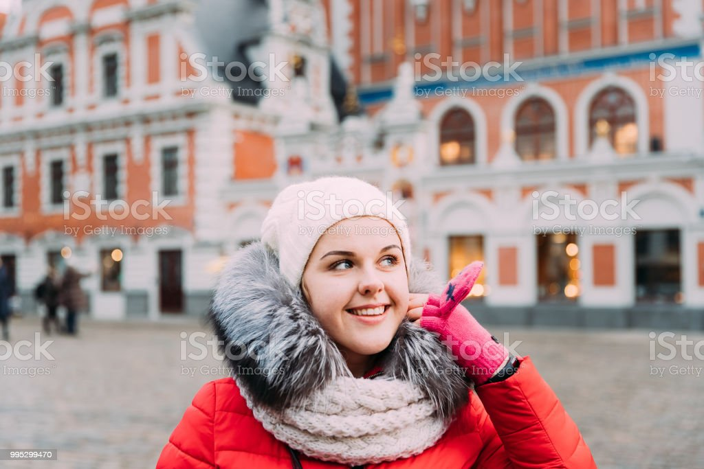 Riga, Latvia. Young Beautiful Pretty Caucasian Girl Woman Dressed In Red Jacket And White Hat Enjoying Life And Smiling On Background Blackheads House stock photo