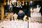 Riga, Latvia - December 18, 2017: Young Woman Seller Sells Various Jewelry Made Of Amber. Traditional Souvenirs At European Market. Souvenir From Baltic Countries, Europe.