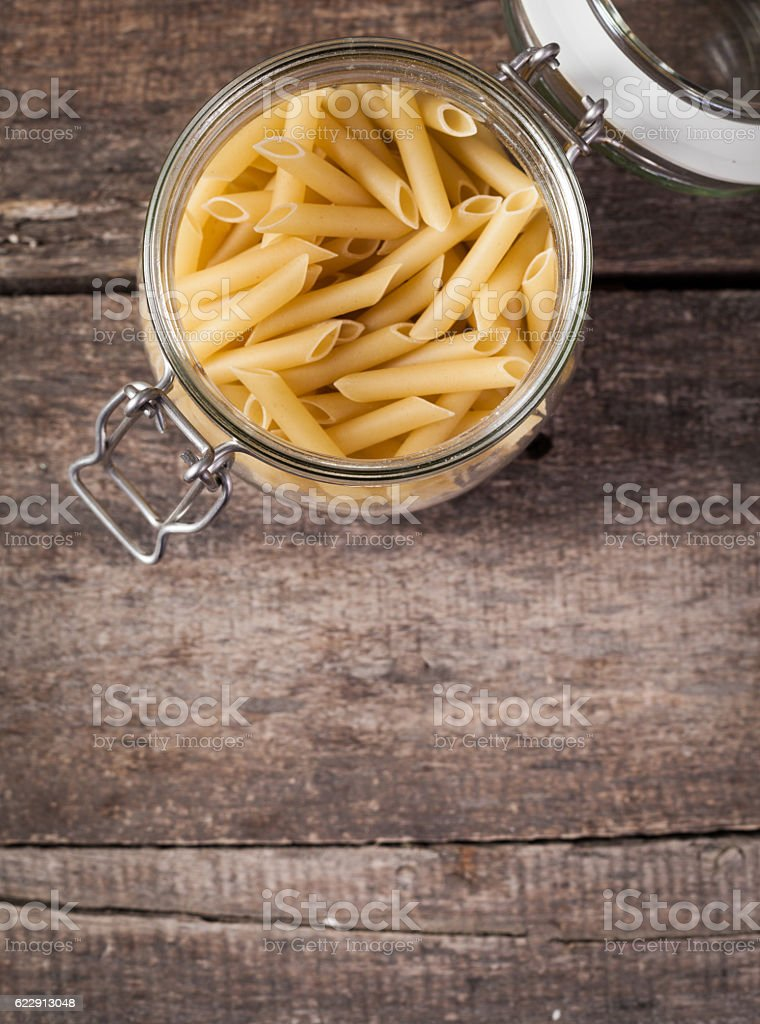Rigatoni pasta or tube shaped pasta over wooden background stock photo