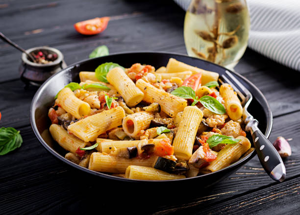 Rigatoni pasta with chicken meat, eggplant in tomato sauce in bowl. Italian cuisine. Rigatoni pasta with chicken meat, eggplant in tomato sauce in bowl. Italian cuisine. rigatoni stock pictures, royalty-free photos & images