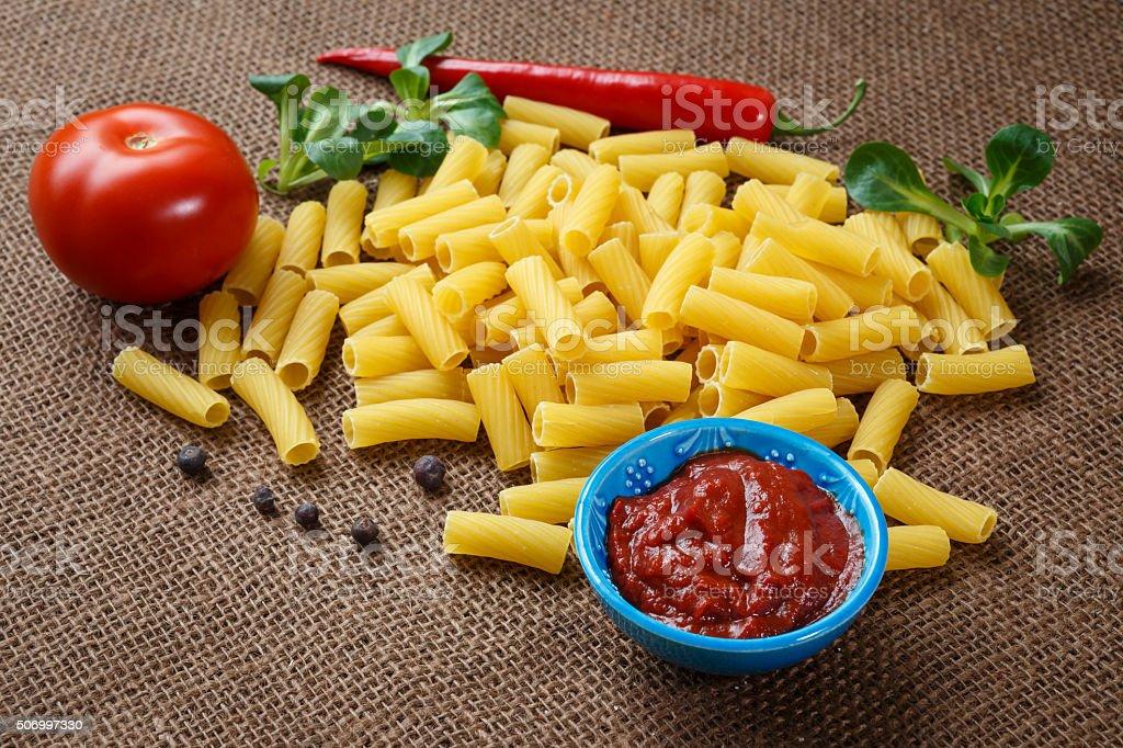 Rigatoni raw pasta on background of jute stock photo