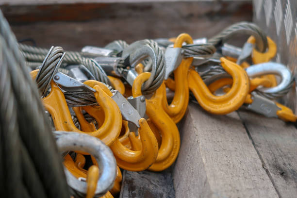 Rigging Equipment Hooks and Wire Slings Closeup of Lifting Equipment - Yellow Grade 80 Sling Hooks attached to Wire Rope Slings. Shallow depth of field rigging stock pictures, royalty-free photos & images