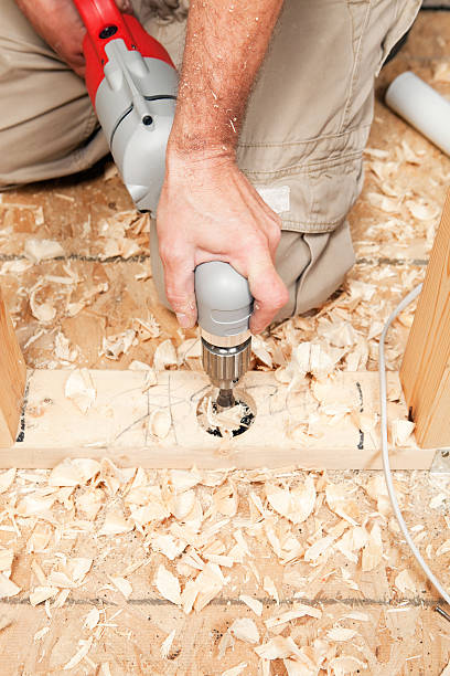 "Right Angle Drill Cutting Hole for Plumbing ""A large right angle drill with a hole bit, is drilling through a house interior wall sole plate and subfloor to run a PVC pipe."" right angle stock pictures, royalty-free photos & images"