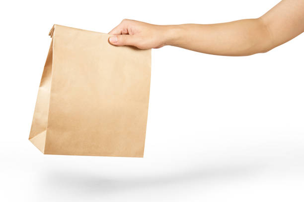 right hand holding a brown paper bag isolated on white with clipping path. - food delivery zdjęcia i obrazy z banku zdjęć