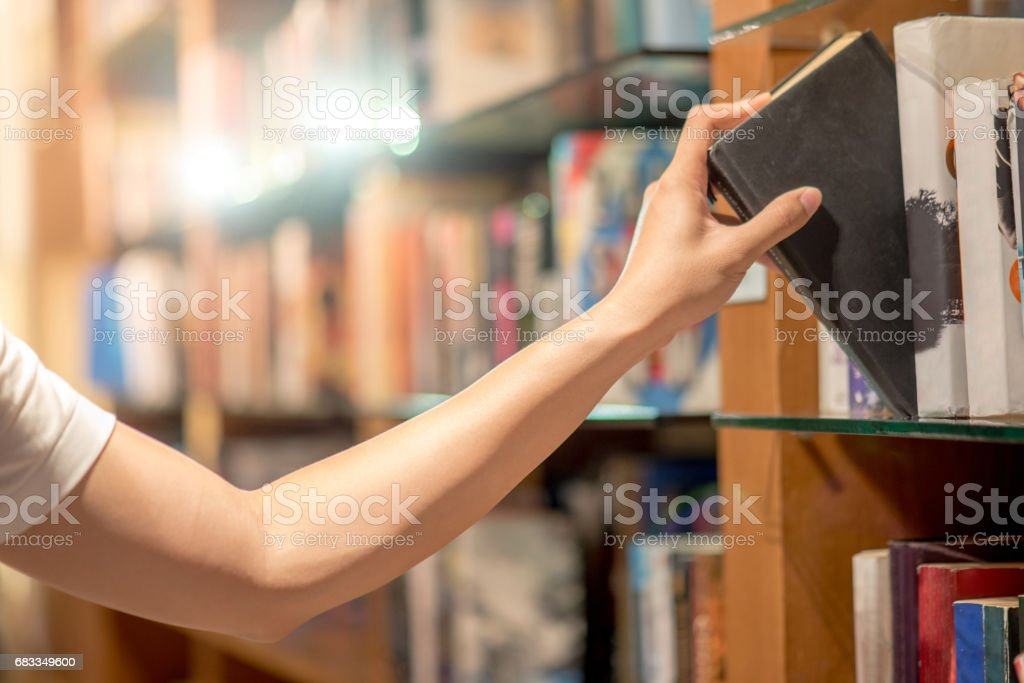 Right hand of young man picking a book from bookshelf in library stock photo