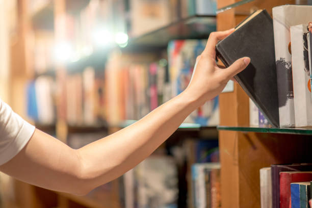 Right hand of young man picking a book from bookshelf in library ストックフォト