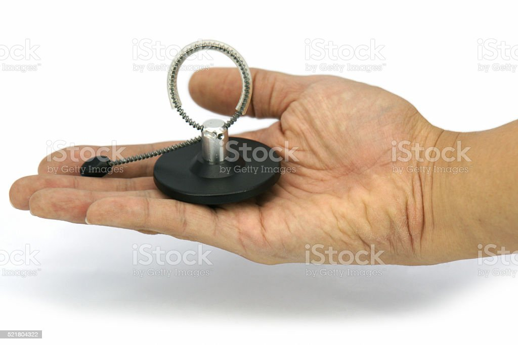 Right male hand hold a magnetic bottle security tag isolated stock photo