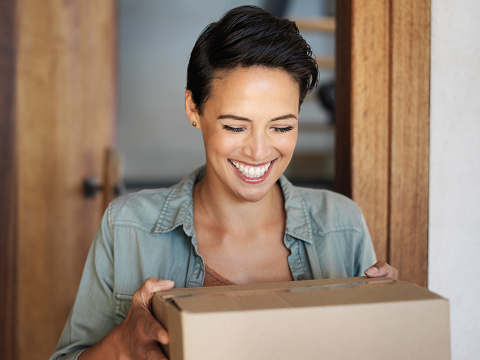 Shot of a smiling young woman standing at her front door receiving a package from a courier