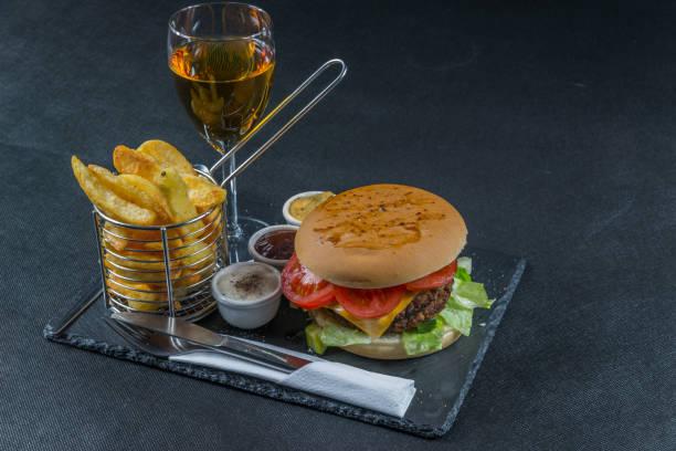 vista lateral direita em um cheeseburger grelhado da pilha dobro da flama, alface, tomate, com três molhos, microplaquetas em uma cesta do metal, vinho branco - foto de acervo