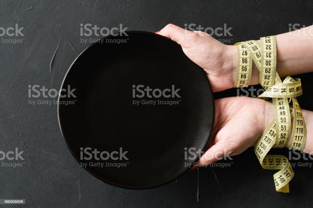 rigid diet fasting weightloss hands empty plate stock photo