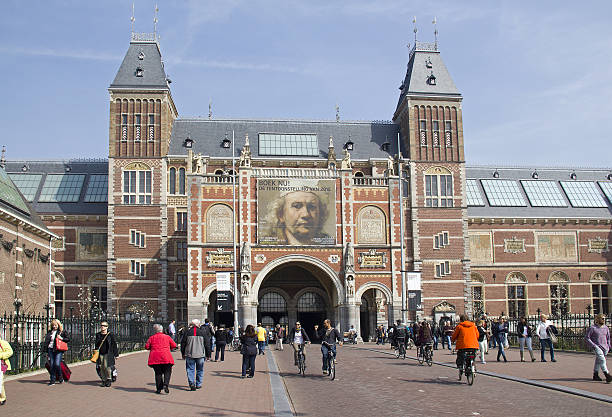 Rijksmuseum Amsterdam, Holland Amsterdam, Holland - April 10, 2015: Tourists and cylcists in front of the Rijksuseum with billboard of Rembrandt exhibition in Amsterdam, Holland on Apil 10, 2015 rijksmuseum stock pictures, royalty-free photos & images