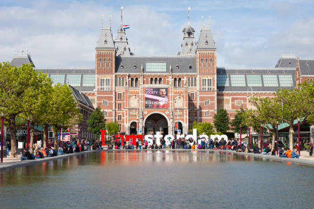 Rijksmuseum Amsterdam Amsterdam, Netherlands - May 17, 2018: Rijksmuseum Amsterdam museum with words I Amsterdam and tourists. Famous landmark in Netherlands, Holland rijksmuseum stock pictures, royalty-free photos & images