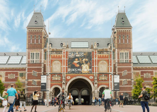 Rijksmuseum building facade with tourists and cyclists in Amsterdam Amsterdam, Netherlands - August 23, 2018: Rijksmuseum building facade with tourists and cyclists on bright summer day in Amsterdam, Netherlands museumplein stock pictures, royalty-free photos & images