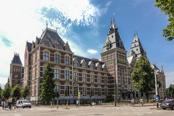 Rijksmuseum facade and central entrance in Amsterdam Netherlands. Amsterdam, the Netherlands - June 30, 2019: Wide shot of Rijksmuseum Monumental facade with towers in beige and red bricks. Under blue-whtie cloudscape. People in front. rijksmuseum stock pictures, royalty-free photos & images