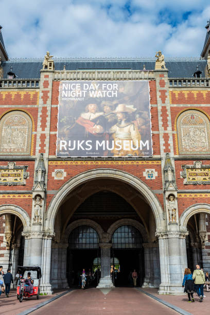 Rijksmuseum (National Museum) in Amsterdam, Netherlands Amsterdam, Netherlands - September 9, 2018: Facade of the Rijksmuseum (National Museum) with an ad for a painting by Rembrandt and people around in Amsterdam, Netherlands rijksmuseum stock pictures, royalty-free photos & images